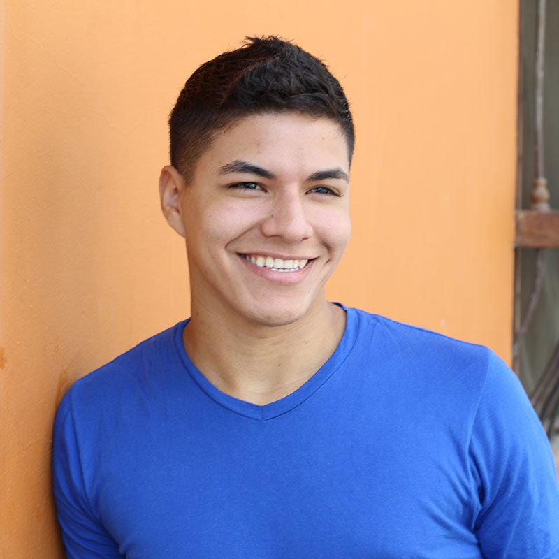 Young man smiling in front of house